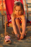 Young girl sitting on sunbed on sand beach - Ambient light makes perfect condition royalty free stock photography