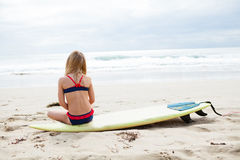 Young girl sitting on surfboard on beach Royalty Free Stock Photography