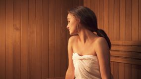 Young girl is sitting at sweating and steam room for skin care treatment. Nature relaxation and healthcare lifestyle at wooden tratidional sauna. Caucasian stock footage