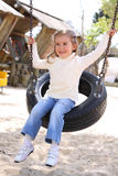 Young girl sitting on a swing. Made from car's wheel royalty free stock photo
