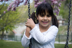 Young girl sitting on swing Stock Images