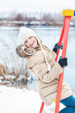 Young girl sitting on swing on bank of winter pond Royalty Free Stock Photography