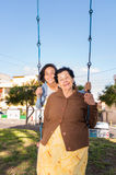 Young girl sitting on swing with grandmother in Royalty Free Stock Photography