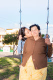 Young girl sitting on swing kissing grandmothers Royalty Free Stock Images