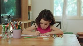Young girl sitting at the table drawing with colored pencils stock footage