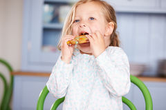 Young Girl Sitting At Table Eating Cookie Royalty Free Stock Photos