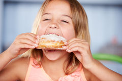 Young Girl Sitting At Table Eating Sugary Donut Royalty Free Stock Photos