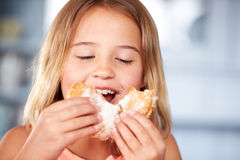 Young Girl Sitting At Table Eating Sugary Donut Stock Photography