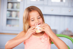 Young Girl Sitting At Table Eating Sugary Iced Bun Royalty Free Stock Image
