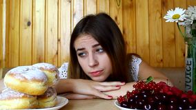 A young girl sitting at a table, looking for food,  diet stock footage