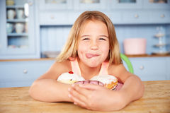 Young Girl Sitting At Table Looking At Plate Of Sugary Cakes Stock Images