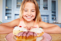Young Girl Sitting At Table Looking At Plate Of Sugary Cakes Stock Photo