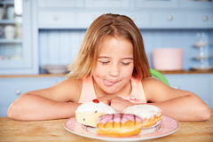 Young Girl Sitting At Table Looking At Plate Of Sugary Cakes Stock Photography