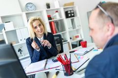 A young girl is sitting at a table in the office, holding glasses in her hand and talking to a man. A slender young girl in a white blouse and blue jacket is royalty free stock photos
