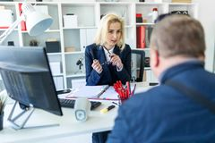 A young girl is sitting at a table in the office, holding glasses in her hand and talking to a man. A slender young girl in a white blouse and blue jacket is royalty free stock images