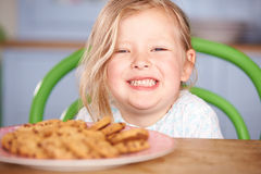 Young Girl Sitting At Table With Plate Of Cookies Royalty Free Stock Image