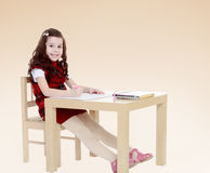 Young girl sitting at the table. Royalty Free Stock Images