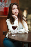 Young girl sitting at table in summer cafe with glass of wine. Young girl sitting at table in summer cafe with a glass of wine royalty free stock photo