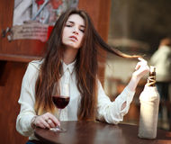 Young girl sitting at table in summer cafe with glass of wine royalty free stock photos