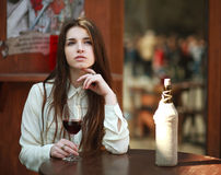 Young girl sitting at table in summer cafe with glass of wine royalty free stock image