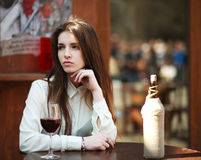 Young girl sitting at table in summer cafe with glass of wine Stock Photography