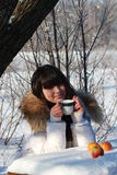 A young girl sitting at a table in a winter forest, drinking tea. A young girl with a cup of tea in the woods Royalty Free Stock Image