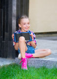 Young girl sitting with a tablet in hands Stock Photos