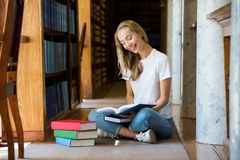 Young girl sitting in traditional old library. Young girl sitting on the floor in traditional old library at bookshelves, reading books.. Smiling and laughing royalty free stock photos