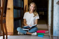 Young girl sitting in traditional old library. Young girl sitting on the floor in traditional old library at bookshelves, reading books.. Smiling and laughing stock image