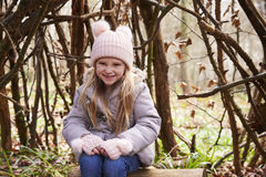 Young girl sitting under a shelter of tree branches Royalty Free Stock Image