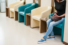Young girl sitting in waiting room on the one of row of blue and ivory chairs in hall. Selective focus. Medicine, business concept Stock Images