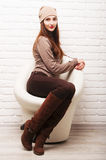 Young girl sitting in a white round chair Stock Photography