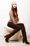 Young girl sitting in a white round chair Stock Photos