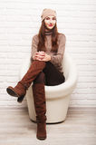 Young girl sitting in a white round chair Royalty Free Stock Image
