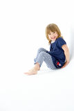 Young Girl Sitting In White Studio Royalty Free Stock Images