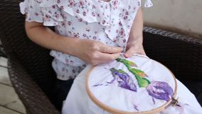 Young girl at cafe sewing with needle. needlework, embroidery, hobby, handicraft stock video