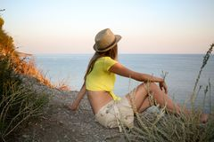 Young girl is sitting on a wild stony sea coast and looking at sea at sunset. Stock Photos