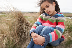 Young Girl Sitting On Winter Beach Stock Photography