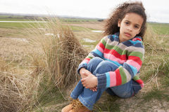Young Girl sitting On Winter Beach Stock Images