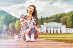 Young girl sitting on wooden alley with book and coffee Royalty Free Stock Photo