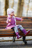 Young girl sitting on a wooden bench Royalty Free Stock Image