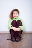 Young girl sitting on the wooden floor Stock Photo