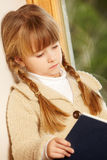 Young Girl Sitting On Wooden Seat Reading Book Royalty Free Stock Photos