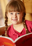 Young Girl Sitting On Wooden Seat Reading Book Stock Images