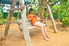 Young girl sitting on the wooden swing with mobile phone Royalty Free Stock Photo