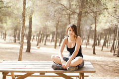 Young girl sitting on a wooden table Stock Photos