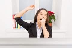 Young girl sitting at work and yawning. Stock Image