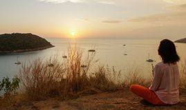 Young girl sitting in yoga lotus meditation position in front to seaside on the rocks an watching the sun goes down in a golden ho stock photo