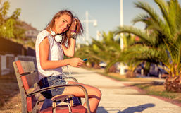 Young girl with skateboard and headphones looking Stock Image