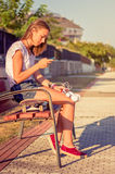 Young girl with skateboard and headphones looking Royalty Free Stock Image